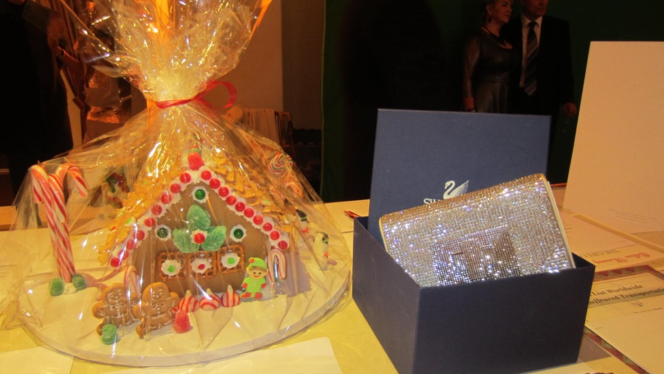 Just two of the gorgeous silent auction items--a gingerbread house, and a Swarovski crystal clutch! Photo by Alice Farinas.
