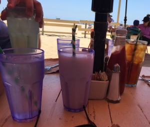 The beverages, in pretty purple glasses.  Mark's hand is clutching his lemonade n the left, and Jeanine's iced tea is on the right.  Everything in the middle is mine! Photo by Karen Salkin.
