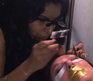 Shareen Adair applying individual lashes to a guest who's wearing their lip mask. Photo by Patty Onanagn.