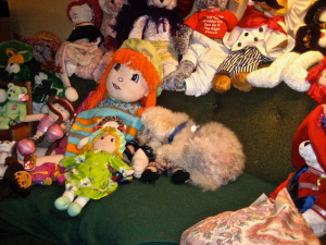 Clarence lying amidst just a few of Maybelle's stuffed pals! Photo by Mr. X.