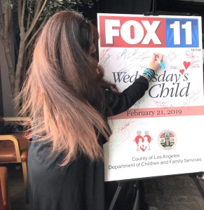 Karen Salkin signing the poster for Wednesday's Child.  Just look at her beautiful tresses! Photo by Noelle Hannibal.