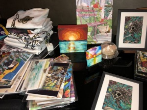 Some of the artwork on offer, clockwise from bottom left: assortment of postcards and tote bags by Karen White, sunset pix by Amy Row, bench painting by Lynne Reichhart, and drawings by Azula Morphoenix.  Photo by Karen Salkin. Click on the pic to make it bigger so you can see the fabulousness in all its glory!