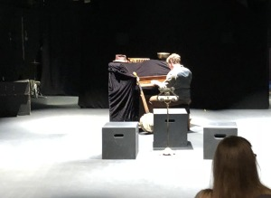 The empty-ish set, with Logen Hone entertaining the crowd as they get seated.  (The piano et al gets moved back and out of the way when the show begins.)  Photo by Karen Salkin.