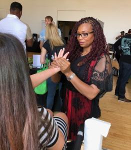 Karen Salkin getting a hand massage from Kelly Anne. Photo by Roz Wolf.