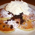 Chocolate chip pancakes with whipped cream.