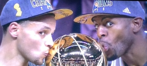 Regular season MVP, Steph Curry, and Finals MVP, Andre Iguodala, kissing the Larry O'Brien Championship Trophy.