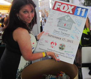 Karen Salkin signing the Wednesday's Child Celebrity Poster, after donating some gifts to the cause. Photo by Nikki D'Amico.