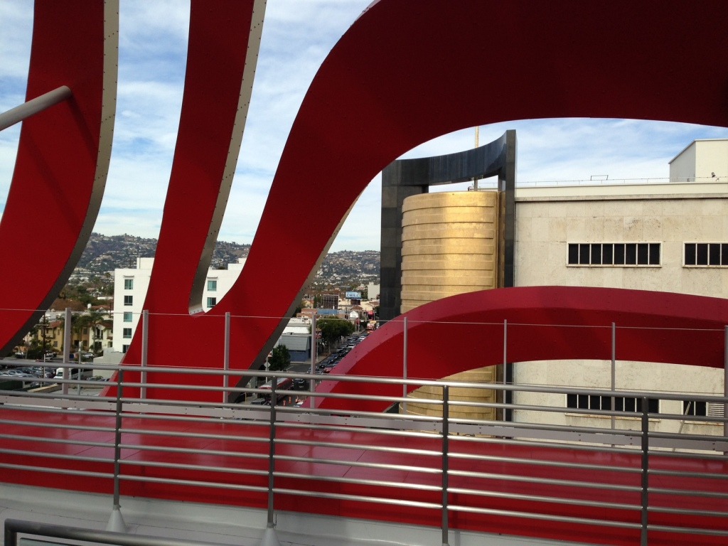 """The view of the """"perfume bottle"""" on the building across the street from the Petersen Musesum, viewed though the exterior stripes, which are red on the inside.  Whew! Photo by Karen Salkin."""