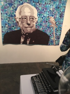 This pic features three things I got a kick out of: a tapestry of none other than Bernie Sanders, a typewriter from 1929(!), and a guest whose dress that matches the tapestry!  What fun! Photo by Karen Salkin.