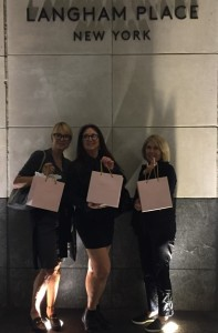 A trio of happy guests, exiting the hotel with their pink goodie bags.