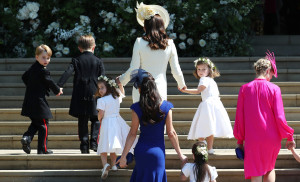 Kate Middleton, in the lowkey cream-colored coat-dress, walking her children into the wedding. (Look at how adorable Prince George is on the far left.)