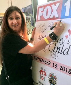 Karen Salkin happily autographing the Wednesday's Child poster, after dropping off a bunch of gifts for the teens. Photo by Nina Herzog.
