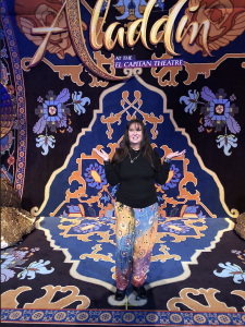 Karen Salkin, posing on the Magic Carpet on the El Capitan stage.  Notice how prescient she was to wear Indian pants that match the carpet, with no prior knowledge!  Photo by Mr. X.
