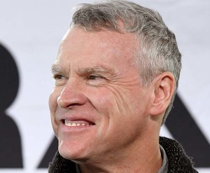 Tate Donovan, with his unkempt eyebrows, and showing the tops of his creepy teeth caps.