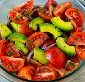 A plate of tomatoes and avocados.