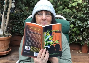 Karen Salkin, sans her usual glamour, being surprised while reading Summer of L.U.C.K. on her deck in this cooler weather.  Photo by Mr. X.