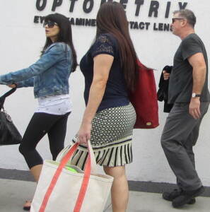 Hilaria and Alec Baldwin walking in Beverly Hills a few years ago, with someone in the middle.  (And no--that is NOT me! She and I do have similar good long, dark hair, but I'm not that big, knock on wood!) Photo by INAM staff.