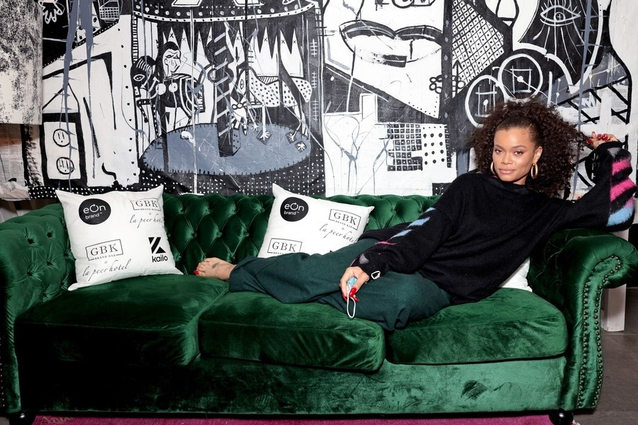 Andra Day lounging at the GBK Brand Bar Pre-Oscars Gift Lounge. Photo by Tiffany Rose.