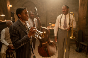 Chadwick Boseman  in front, holding the trumpet.