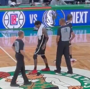 Rotten Brooklyn Net Kyrie Irving rubbing his foot on the logo of his former team, the Boston Celtics.
